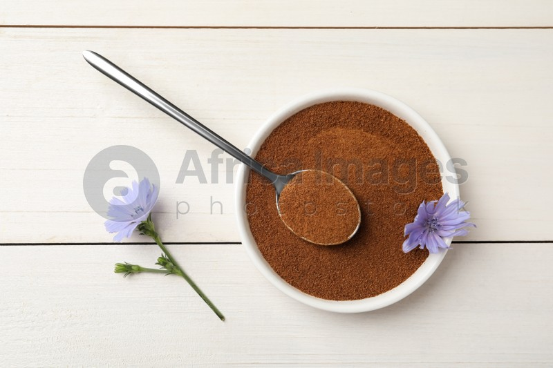Bowl of chicory powder and flowers on white wooden table, flat lay