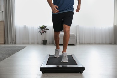 Sporty man training on walking treadmill at home, closeup