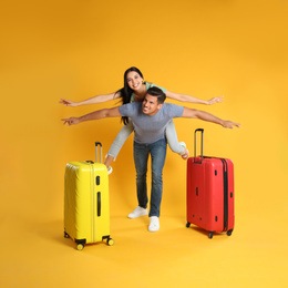 Happy couple with suitcases for summer trip on yellow background. Vacation travel