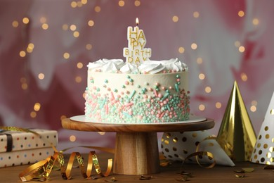 Beautiful birthday cake with burning candle and decor on wooden table