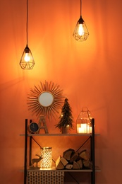 Shelving unit with Christmas decor and firewood near orange wall. Interior design