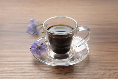 Glass cup of delicious chicory drink and flowers on wooden table