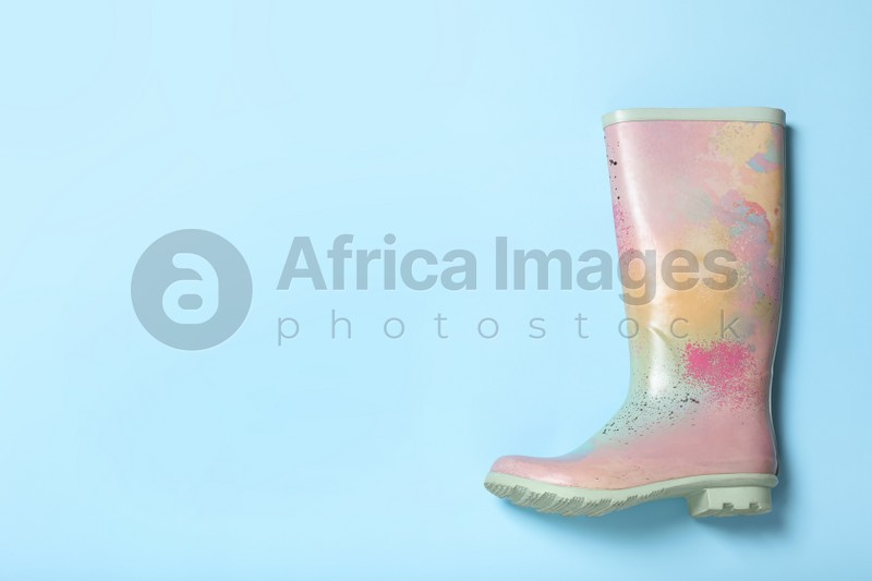Colorful rubber boot on light blue background, top view. Space for text
