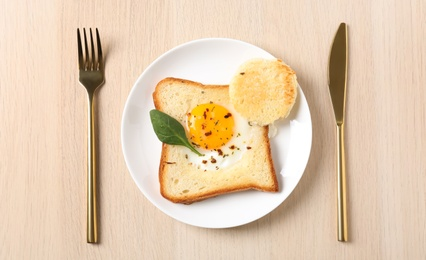 Tasty toast with fried egg served on wooden table, flat lay