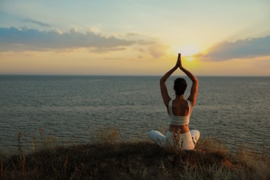 Woman meditating near sea, back view. Space for text