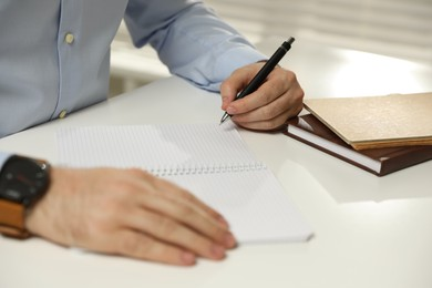 Left-handed man writing in notebook at white table, closeup
