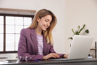 Young woman working on laptop in office