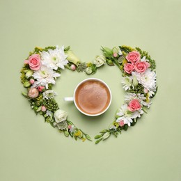 Beautiful heart shaped floral composition with cup of coffee on light green background, flat lay