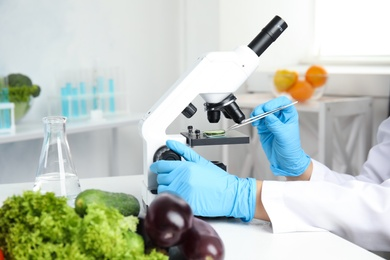 Scientist inspecting slice of cucumber with microscope in laboratory, closeup. Poison detection