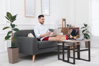 Businessman wearing shirt and underwear during video call at home