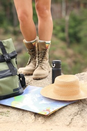 Camping equipment and woman in boots on rock, closeup