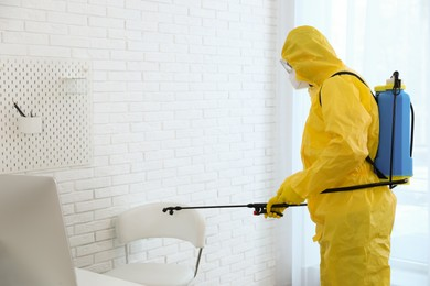 Employee in protective suit sanitizing office. Medical disinfection