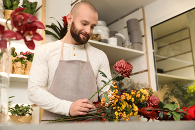 Florist making bouquet with fresh flowers at table in shop