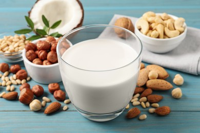 Vegan milk and different nuts on light blue wooden table