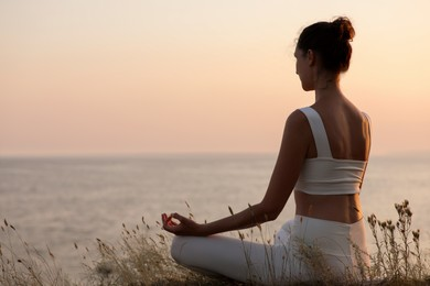Woman meditating near sea. Space for text
