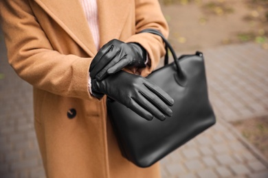 Young woman in black leather gloves, closeup. Stylish clothes