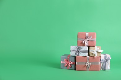 Many beautifully wrapped gift boxes on green background. Space for text