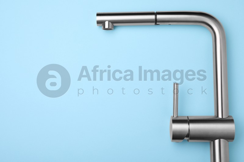 Modern pull out kitchen faucet on light blue background, top view. Space for text