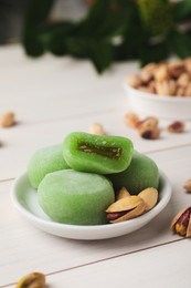 Delicious mochi and pistachios on white wooden table, closeup with space for text. Traditional Japanese dessert