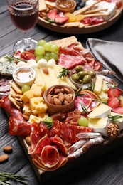 Tasty assorted appetizers served on black wooden table