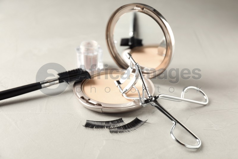 Eyelash curler and makeup products on grey table, closeup