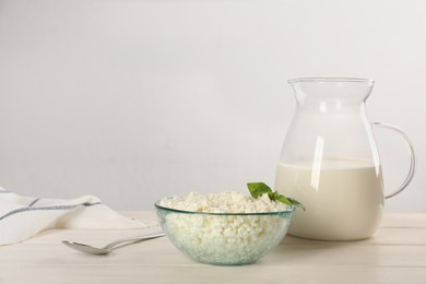 Delicious fresh cottage cheese with basil and milk on white wooden table. Space for text