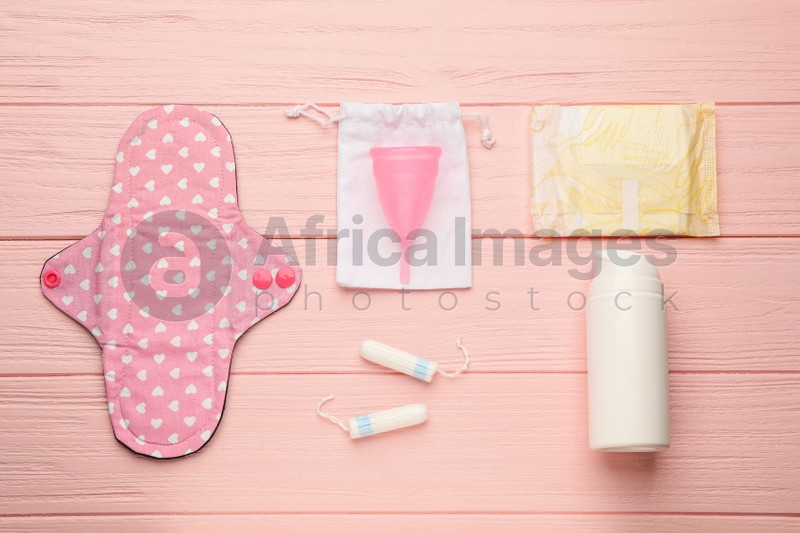 Cloth menstrual pad and other female hygiene products on pink wooden table, flat lay