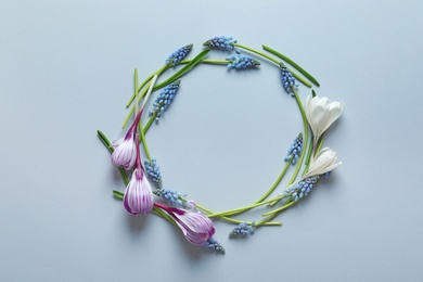 Beautiful spring crocus and muscari flowers on color background, top view with space for text