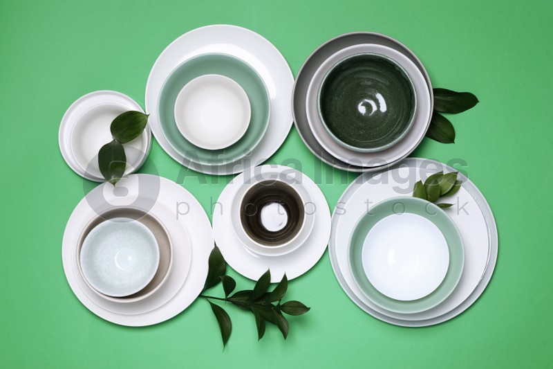 Different dishware and leaves on green background, flat lay