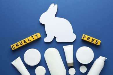 Cubes with text Cruelty Free, personal care products and figure of rabbit on blue background, flat lay. Stop animal tests