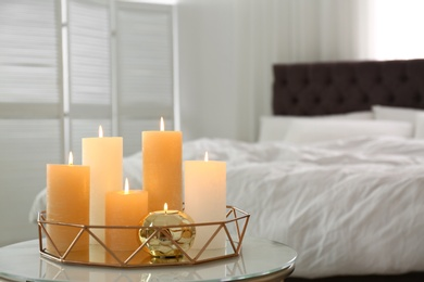 Golden tray with burning candles on table in bedroom