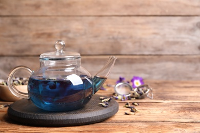 Organic blue Anchan in glass pot on wooden table, space for text. Herbal tea