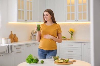 Young pregnant woman with smoothie in kitchen. Healthy eating