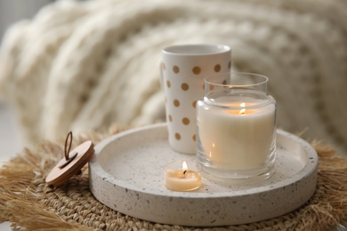 Cup of drink and burning candles on wicker mat indoors. Interior elements