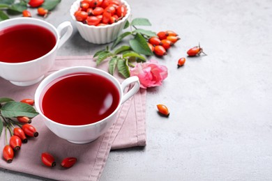 Fresh rose hip tea and berries on light table. Space for text
