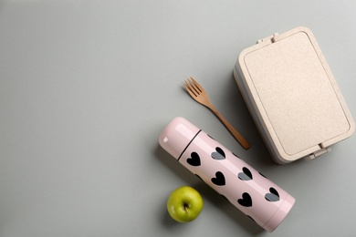 Thermos, lunch box with cutlery and apple on light grey background, flat lay. Space for text