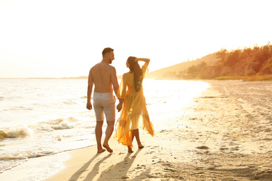 Happy couple walking together on beach at sunset, back view