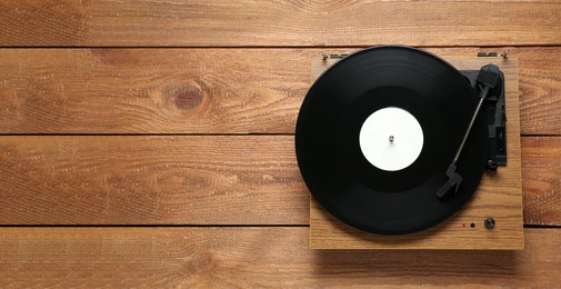 Turntable with vinyl record on wooden background, top view. Space for text