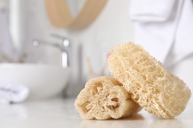 Natural loofah sponges on table in bathroom, closeup. Space for text