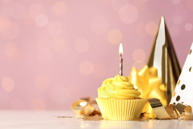 Delicious birthday cupcake with cream and burning candle on white table. Space for text
