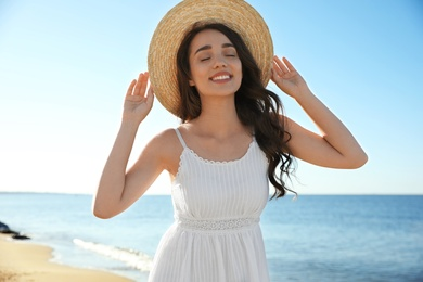 Happy young woman with beach hat near sea