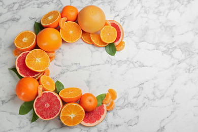 Letter C made with citrus fruits on marble table as vitamin representation, flat lay. Space for text