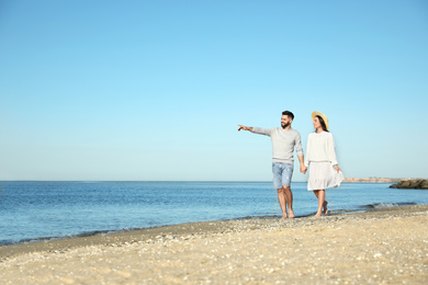 Happy young couple walking on beach near sea. Honeymoon trip