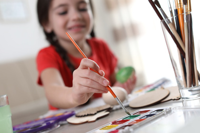 Little girl painting decorative egg at table indoors, focus on hand. Creative hobby