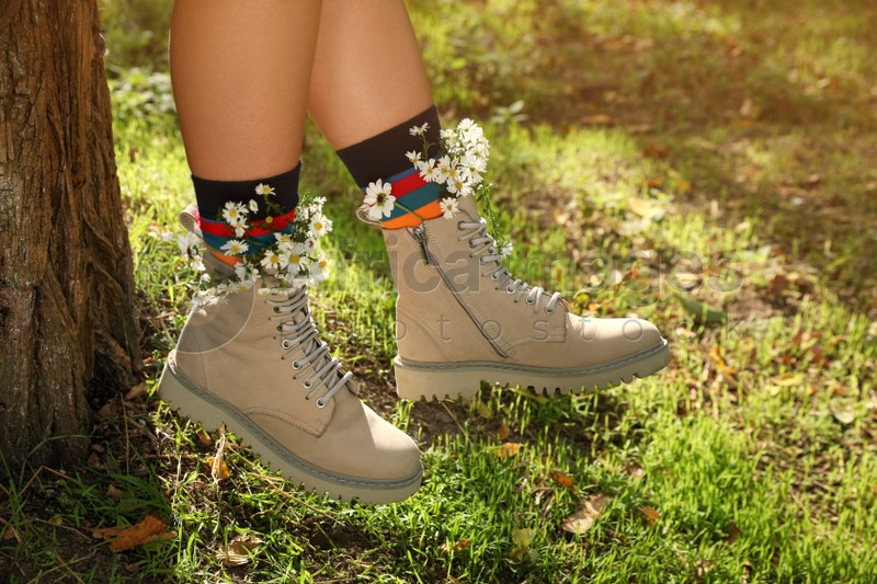 Woman with beautiful tender flowers in socks outdoors, closeup