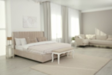 Blurred view of stylish hotel bedroom interior with modern furniture
