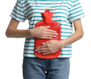 Woman using hot water bottle to relieve abdominal pain on white background, closeup