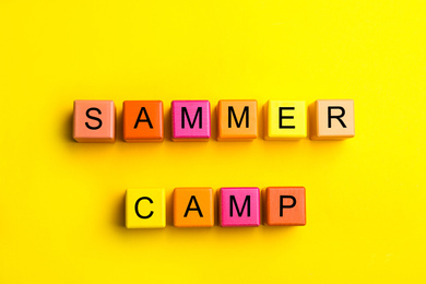 Colorful wooden cubes with phrase SUMMER CAMP on yellow background, flat lay