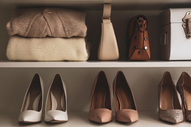 Stylish women's shoes, clothes and bags on shelving unit