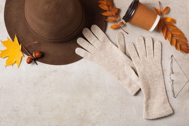 Flat lay composition with stylish woolen gloves, hat and dry leaves on beige table. Space for text